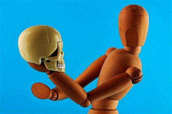 Wooden Dummy holding a plastic skull