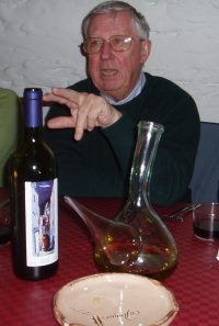 Sam Roxburgh points at a bottle of wine