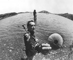 Image Shows Salvador Dali holding a seashell as he sails out to sea